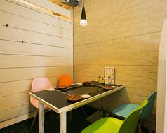白を基調とした空間に、カラフルなデザインチェアがアクセント!店内奥のテーブル席は、少人数の飲み&お食事会や、お打ち合わせシーンにもぴったりです。お手元の鉄板でお好み焼きや新鮮食材を焼きながら、楽しいひとときをどうぞ。