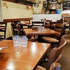 ライブ感ある1Fテーブル席 / ピッツァ窯のすぐ近くのお席、職人が1枚1枚焼き上げる姿をご覧いただけます。