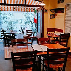 臨場感を味わえる1Fテーブル席 / ピッツァ窯を眺めながらお食事できる1階席、入口近くにはテラス席もあり、開放感が感じられます。