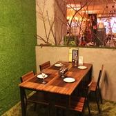 4名テーブル席は、森の中の秘密基地のよう♪緑の芝生みたいな壁に、木の装飾が◎