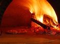 当店のピザは、一般のピザよりも高温で焼き上げる「本格薪窯焼き」ピザです。