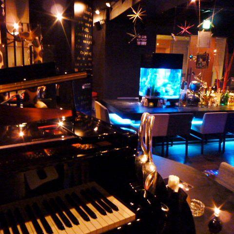 薄明かりの店内に揺れるキャンドルの炎。そして、存在感たっぷりの透明度100%の熱帯魚水槽。グランドピアノによるJAZZの生演奏も魅力。