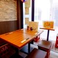 窓際の4人テーブル席です。美味しい串焼きと鉄板料理、お酒をお楽しみください