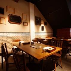 レンガ調の壁がお洒落な店内のテーブル席です。木のぬくもりが感じられ、落ち着いてお食事をいただけます〇
