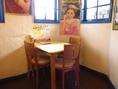 少人数向けのテーブル席はテーブル面がイエロー。白い壁とブルーの窓枠と相まって爽やかな印象。