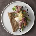 料理メニュー写真蕎麦粉のガレットに乗せたグルメなシーザーサラダ 24ヶ月熟成のパルメザンの削り出し