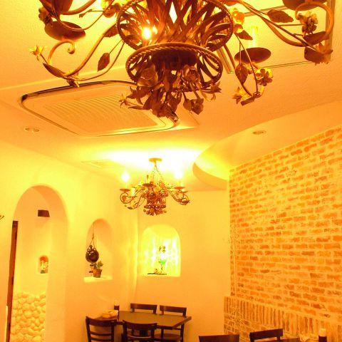 写真は最大26名様の個室。アンティークシャンデリアと南欧風の白壁がパーティー向きです。