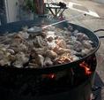 まず鍋をまきで熱し、大きな鍋に骨付きの鶏肉を入れて炒め、そのあとに野菜を入れじっくり炒める。食材を炒め終えたら水を入れる。※水を入れたらここでしっかり骨付きの鶏肉からダシを取るのがポイント♪※