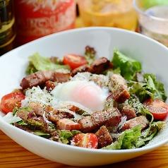 料理メニュー写真炙りベーコンと温泉玉子のシーザーサラダ