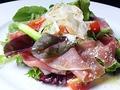 料理メニュー写真生ハムとグラナバダーノのシーザーサラダ