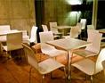 コンクリートの打ちっぱなしの壁と白を基調とした店内。各イベントに合わせテーブル、椅子をすべて片付けてフルフロアーでご利用も可能ですし、ステージ方向に並べたりと色々レイアウト変更出来ます。