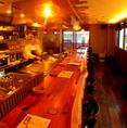 オレンジ色の照明と、高級感のある大きな一枚板の木のテーブルが自慢のカウンター席