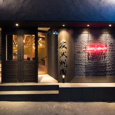 黒い龍のウロコのような壁にベンジャミンランチの赤いネオンが目印