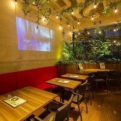 【フリーWi-Fi・全卓コンセント完備】大きな壁面スクリーンと植物のコントラストが楽しめるテーブル席です。パーティー等でプロジェクターとしてもご利用いただけます。