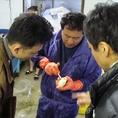 漁師の方から新鮮な魚介類の説明をうけています