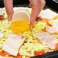 生地が伸びたら、トッピング♪トマトソースを伸ばし、チーズをふんだんに散りばめます。手切りにしたベーコンを乗せたら、仕上げに真ん中に生卵。これで準備OK☆