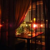窓側の夜の街灯差し込むお洒落な半個室ソファー席