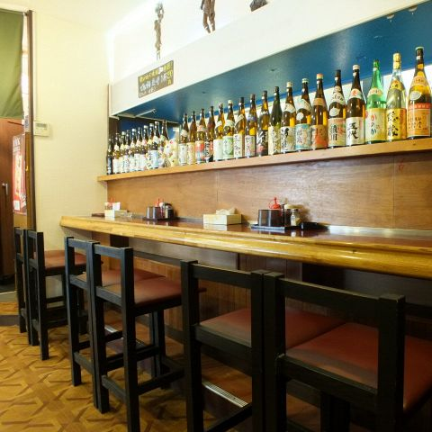 木造りのカウンターではおひとり様でも寛いで頂けます。目の前に立ち並ぶ日本酒のビンが圧巻。