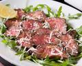 料理メニュー写真黒毛和牛もも肉のタリアータ ルーコラのサラダとパルミジャーノ
