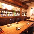 【1F】大きなテーブル席も完備しております♪壁には泡盛がずらりと、お席に彩を加えています。沖縄を感じる雰囲気をお楽しみください。