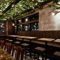 【2~20名/店右テーブル席】奥にはベンチシート、手前にはブラウンのふかふかスツールを配置したウッディーなテーブル席。天井にはフルーツ農園でピクニックをしているような緑あふれる明るい空間が拡がります。少人数での気軽なお食事からご友人との宴会、同僚との打ち上げなどにご利用ください。