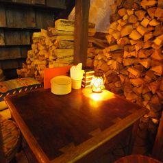 【3F】階段下のテーブル席もこじんまりしていてカップルや女性同士に人気の場所♪薪が無造作に積み上げられているのとテーブル上の照明が暖かい雰囲気を醸し出す☆