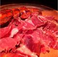 料理メニュー写真切りたて生ハムと濃厚イベリコ豚のサラミの盛り合わせ