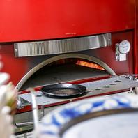 オープンカウンターからは存在感のある赤い本格ピザ窯