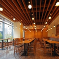 メインダイニングフロアには、合計84席のテーブル席がございます。開放感たっぷりの高い天井から伸びる優しいランプが照らし出す、木の温もりが溢れる空間です。