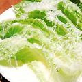 料理メニュー写真ガーリックをきかせたドレッシングと削りたてチーズをたっぷりかけたロメインレタスのシーザーサラダ