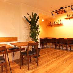 白を基調としたシンプルで落ち着いた雰囲気の壁と、木の暖かみを感じられるテーブル席