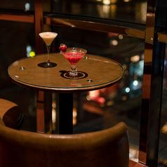 2名様テーブルは窓側にてご用意。夜景とともに選りすぐりの素材を使ったカクテルをお楽しみください。