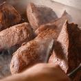 黒毛和牛ローストビーフを仕込んでいる風景です。高温の鉄板で表面を焼き付け、旨味を閉じ込めるように低温調理。一緒に当店自慢の出汁とスパイスシーズニングで味を入れています。