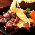 料理メニュー写真牛サイコロステーキ  ラクレットチーズ掛け