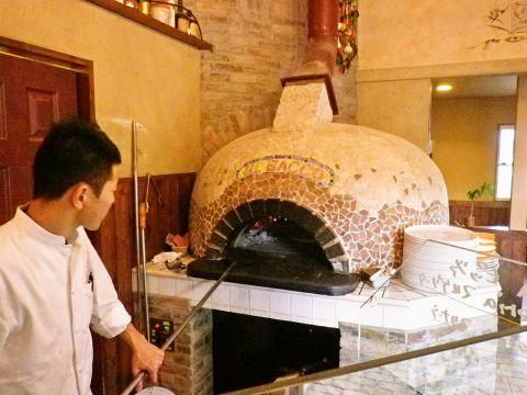 ピッツアを焼き上げる薪窯が丸みを帯びてキュート。壁に掲げられたステキな絵画&テラコッタの床も居心地の良さを演出。