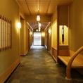 リニューアル後も続く明治21年創業の風格を保った創りの通路。高い天井は落ち着いた雰囲気を作り木造の椅子や扉が落ち着きを作り出す。
