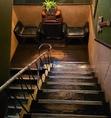 1階と2階を繋ぐ真鍮のステップがついた階段。座るだけで絵になる革張りのベンチシートも。