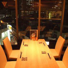 壁で仕切られ夜景も楽しめるテーブル席