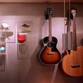 壁に掛けられたミニチュアの椅子とアコースティックギター。