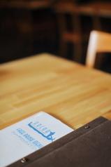 広々とした温かみのある木製のテーブル。カップルやご家族連れでも安心のパーテーションによる半個室も可。