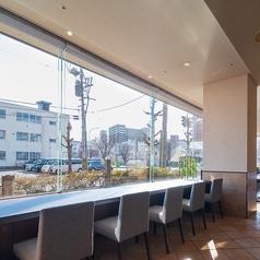 大きな窓から陽光が差し込むカウンター席
