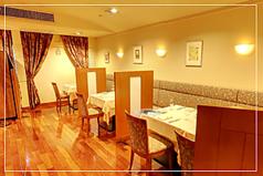 温かみのあるカリン材の床と、広々とした空間。パーテーションで仕切られ、落ち着いたテーブル席です。