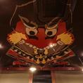 五島列島の伝統民芸「バラモン凧」!縁起物として贈られる民芸凧が「つばき庵 新橋店」天井に!長崎県五島列島に古くから伝わる民芸品で、「バラモン」とは「荒々しい、活発、元気のいい」という意味の方言です。鬼が武士の兜をくわえこんだ姿が描かれており、羅生門の鬼退治の伝説を表現していると言われます。