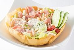 料理メニュー写真生ハムと蒸し鶏の温玉シーザーサラダ