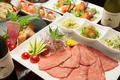 料理メニュー写真薄切り炙り牛タンの熔岩石焼き~三種の野菜の薬味と共に~