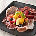 料理メニュー写真パルマ産 生ハムと季節フルーツの盛り合わせ