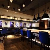 【2名~8名様】青い椅子にランプ、アートが飾られ活気のあるエリア。おおきなテーブルには充電口もあり。