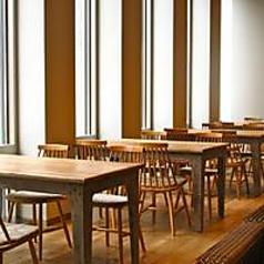 大きな窓から日差しが差し込むゆったりとした木製のテーブル席♪
