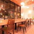 1階のコミュニティーテーブルは他のお客さんやスタッフとの交流も楽しめる憩いの場に…ガラス張りの吹き抜けで開放感ある空間と目の前で職人が調理するLIVE感溢れるオープンキッチンはアットホームで落ち着く雰囲気を創る