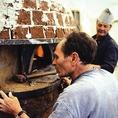 ナポリの窯職人が作ったピザ釜で焼き上げます機械式ではなく、原始的な耐火レンガを使用した窯だからこそ、再現できる450°c~500°cという火力。本場イタリア・ナポリで数々の窯を生んできた伝統の技で、ここ名古屋の地にそれを再現しました。(写真:窯作りの様子)
